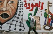 حاج فلسطيني يمشي أمام جدارية العودة في أحد المخيمات.jpg