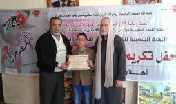 توزيع شهادات التقدير على احد الطلبة المتفوقين في مخيم النصيرات