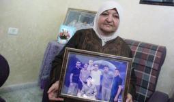 فلسطين المحتلة - أم ناصر أبو حميد تحمل صورة أبنائها الأسرى في سجون الاحتلال