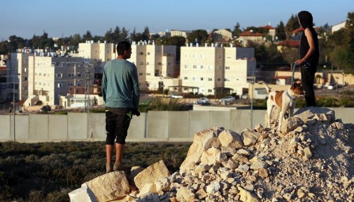 """صورة توضيحية، فلسطينيون من مخيّم الجلزون للاجئين يطلّون من وراء الجدار على مستوطنة """"بيت ايل""""، في الضفة الغربية 7 أبريل، 2015. AFP PHOTO/ABBAS MOMANI"""