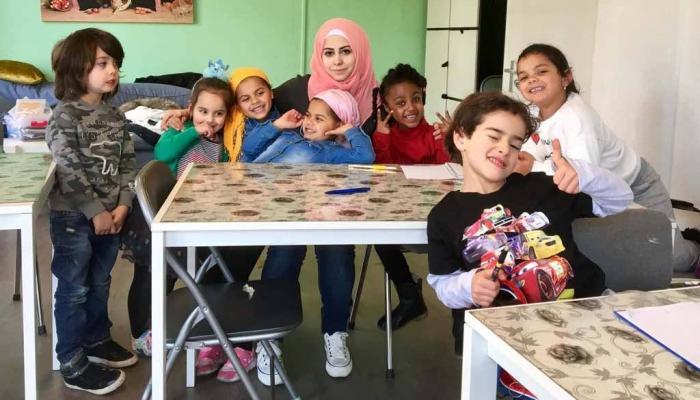 الفلسطينية داليا عبيد مع الأطفال الذين تعلمهم اللغة العربية