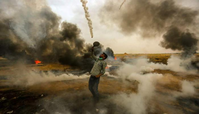 صورة لشاب فلسطيني في مسيرة العودة يصد قنابل الغاز التي يُطلقها الاحتلال بمضرب تنس