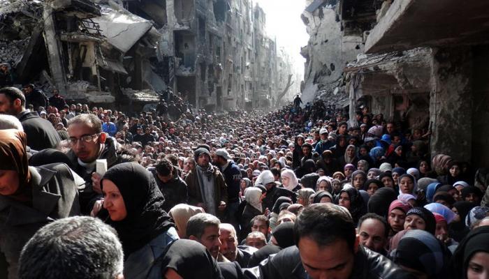 """صورة التقطتها وكالة """"أونروا"""" لجموع اللاجئين المحاصرين على مدخل اليرموك عام 2015"""